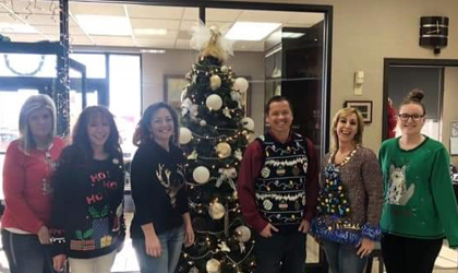 EUCCU employees in Christmas sweaters standing next to the Angel Tree.