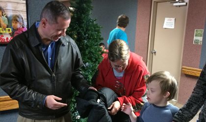 EUCCU's president giving a coat to a student at the Castle Valley Center.
