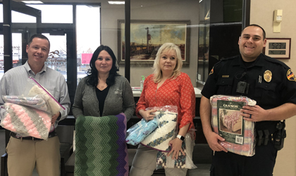 EUCCU employees giving quilts to a police officer.