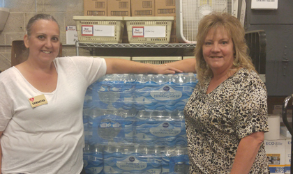 An EUCCU employee standing next to a pallet of waters to be donated for relief from the Texan hurricane.